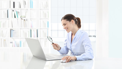 smiling woman in office search on computer with magnifying glass sitting at the desk