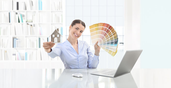 interior design concept smiling woman showing color palette and house model in her hands at desk with computer on office background