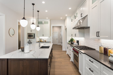 Kitchen in New Luxury Home with Large Island, Pendant Lights, Oven, Range, and Hood, and Hardwood Floors.
