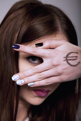 Young serious woman looking through fingers and hand drawn with money as a symbol of bribery, cheating, corruption, financial and l political manipulation.