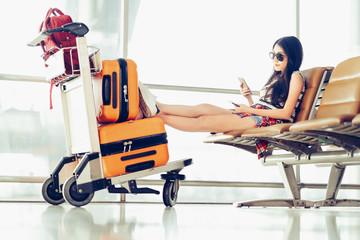 Young Asian traveler woman, university student sit using smartphone at airport, luggages and bag on trolley cart. Online check in mobile app, study abroad, or international tourism lifestyle concept