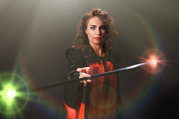 Beautiful woman in the image of a sorceress rotates in her hands a magic staff that emits bright colored flashes