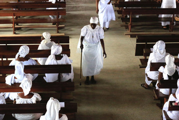 A old woman, a member of the Harris Church, walks during a worship session at their church in Abobo Baoule, Abidjan