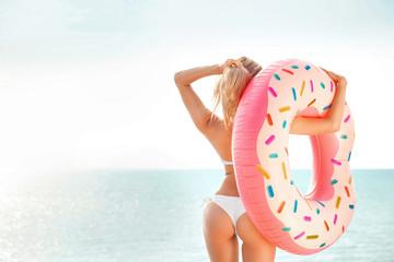 Summer Vacation. Enjoying suntan woman in white bikini with donut mattress near the sea.