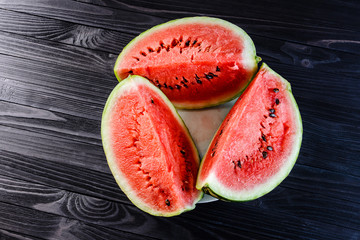 Background of three slices of a cut watermelon in a white plate on a black wooden table top view.