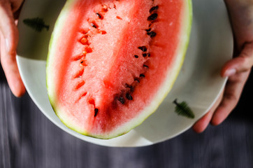 Slice of watermelon on white plate in woman hands ready for eating, top view with blurry black wood table background