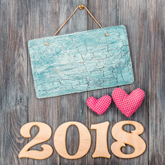 2018 date with handmade hearts and aged sign board blank on vintage old painted wooden wall planks texture background. Retro style filtered photo