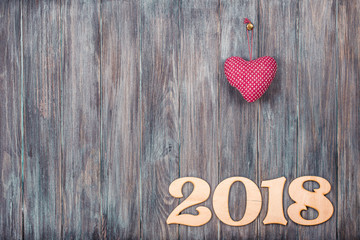 2018 date with heart shape blank on vintage old painted wooden wall planks texture background. Retro style filtered photo