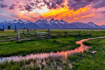 Golden Fiery Sunset at Grand Teton - A colorful spring sunset at Teton Range, seen from an abandoned old ranch in Mormon Row historic district, in Grand Teton National Park, Wyoming, USA.  Wall mural