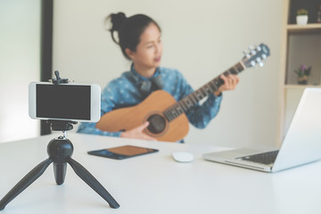 Young female blogger with smartphone recording video at home. beauty and technology concept