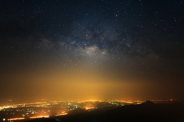 milky way galaxy with stars and space dust in the universe and city light at Phutabberk Phetchabun in Thailand.