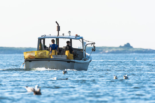 Lobster men hard at work on a beautiful morning in early autumn in South Bristol, Maine, United States