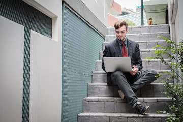 Looking for direction and inspiration, Portrait of happy young businessman sitting with laptop