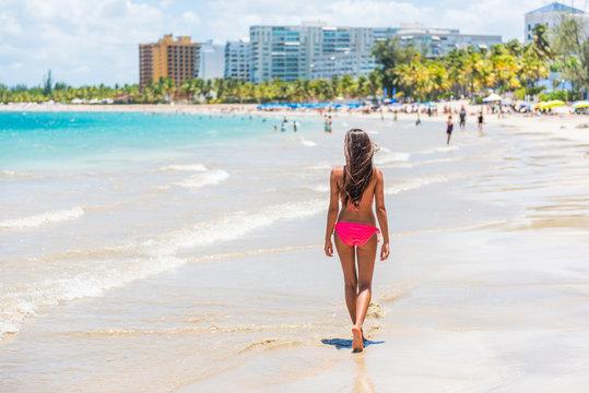 Puerto Rico beach people bikini woman walking on Isla Verde, San Juan. Famous Hispanic travel destination resort beach in Puerto Rico. Swimsuit latina girl relaxing on summer vacation.