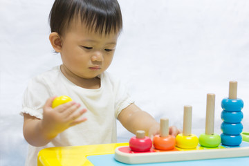 Asian adorable baby one year is playing colorful puzzle pyramid for kid.