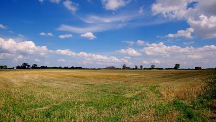 Piękne pogodne niebo, skoszone pole, kopalnia w tle - urok polskich równin