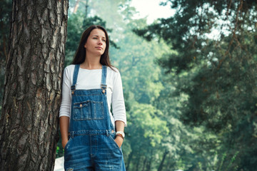 Young woman in jeans overalls standing under tree in woodland Wall mural