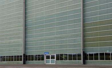 """Hangartor mit einer Tür mit einem Schild """"Eingang"""""""