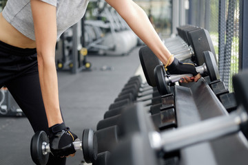 Fit woman wearing sports clothes weighing dumbbells in hands during workout in modern gym