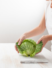 Women's hands are preparing the cabbage on white table