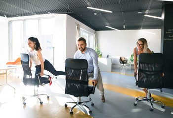 Wall Mural - Business people riding a chair and racing in the workplace.