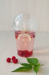 Water with lemon and raspberry in a glass