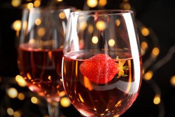 Glasses of delicious strawberry wine against defocused lights