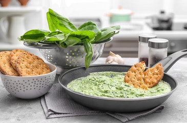 Frying pan with tasty spinach sauce on table
