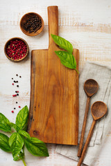 Black and red pepper, basil leaves,  ceramic pan,  wooden stand, simple old spoons and  linen napkin on light background. Kitchen accessories concept. Selective focus. Top view.