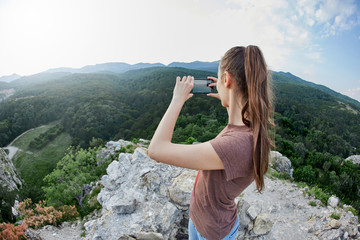 back view of young woman photographing the mountain landscape by smartphone camera at the sunset