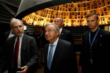 UN Secretary General Guterres looks at pictures of Jews killed in the Holocaust during a visit to the Hall of Names at Yad Vashem Holocaust History Museum in Jerusalem