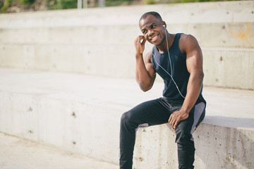 shot of attractive runner with muscular athletic body. Young jogger listening to meditative music with earphones