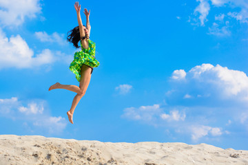 Beautiful woman in bright green dress flies and hovers on the sky. Girl  jumping and feels from prejudice. Beauty and dynamics in flight. Concept of faith in oneself and freedom