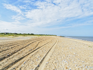 On an empty beach at Caister-on-Sea on the UK's Norfolk coast a group of deep tyre tracks in the sand lead off into the distance on a summer day..