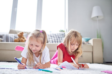 Portrait of two little girls drawing and coloring pictures lying on floor in cozy living room