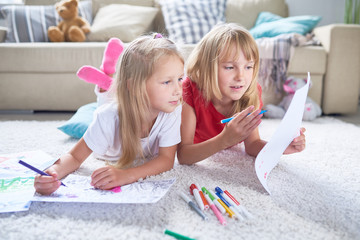 Portrait of two little sisters coloring pictures together lying on floor in cozy living room at home