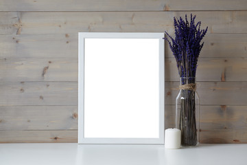 Mother's Day, Women's Day or other suitable holiday card in rectangular photo frame with blank space for your text on white table with lavender flowers bouquet in glass bottle and paraffin candle