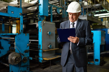 Portrait of senior businessman  wearing hardhat in workshop of  modern factory making notes on clipboard, copy space