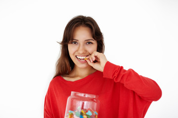 Horizontal isolated picture of charming mixed race teenage girl with brown hair relaxing at home holding big glass jar with candies, looking at camera, chewing jelly beans, gummy bears or marmalades
