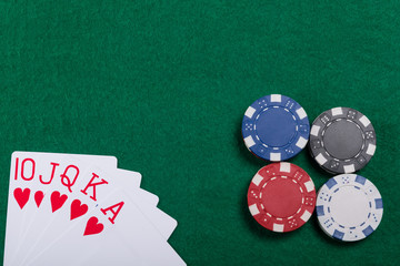 Game chips and cards on the green poker table. A winning combination in Royal Flush poker