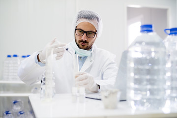 Man researcher is surrounded by medical vials and flasks.