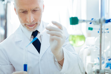 Serious bearded male person looking at test tube