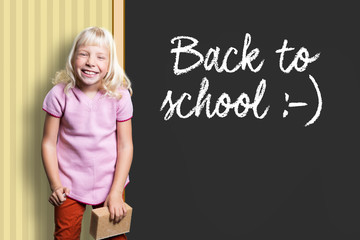 """young girl in front of a blackboard with the sentence """"Back to School"""""""