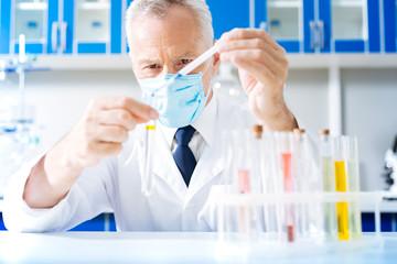Confident practitioner adding blue liquid into tube