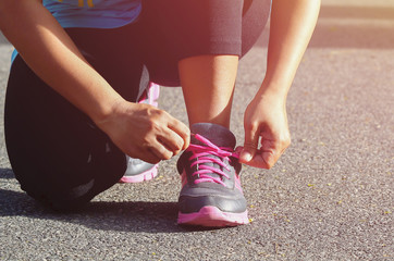Woman tying sports her shoe. Prepare for run in the park