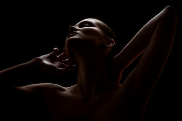 aroused woman posing sensually holding head up on black background