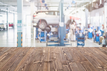 Brown wooden table free space and blurred background of car technician repairing the car in the shop, garage or service station. Use for product display or product montage design