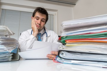Bureaucracy in medicine concept. Tired overworked doctor is reading medical report. Many documents on desk.