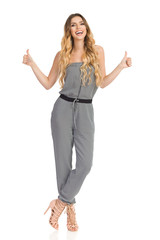 Talking Young Woman In Jumpsuit Is Showing Thumbs Up