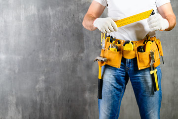 unidentified handyman standing with a tool belt with construction tools and holding roulette against grey background with copyspace. DIY tools and manual work concept
